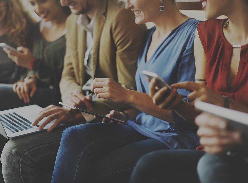 Sohvalla istuva ryhmä ihmisiä erilaisten mobiililaitteiden kanssa